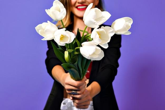 Afbeelding van boeket van witte tulpen in handen van jonge modieuze vrouw in zwarte jas geïsoleerd op paarse achtergrond. Gratis Foto