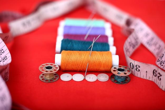 Afbeelding van draden, naalden, spoel, meetlint en knoop. Premium Foto