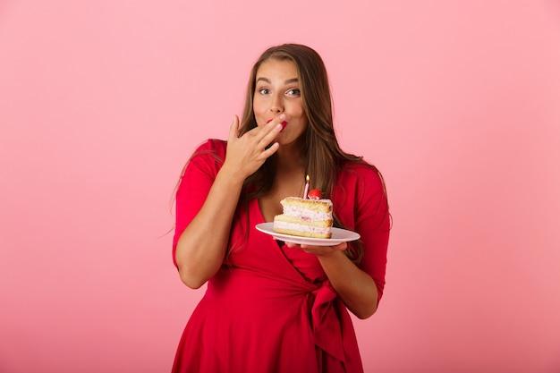 Afbeelding van een gelukkige jonge vrouw geïsoleerd over de roze cake van de muurholding. Premium Foto