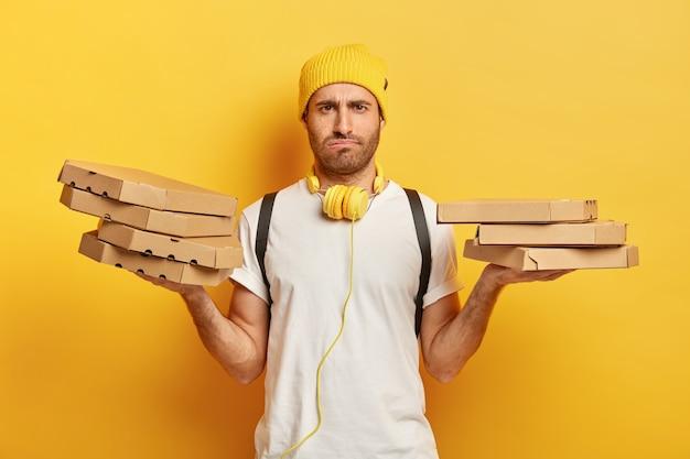 Afbeelding van een ontevreden blanke man heeft een norse gezichtsuitdrukking, houdt kartonnen pizzadozen vast, voelt zich moe nadat hij de hele dag eten heeft bezorgd, draagt een casual outfit, geïsoleerd op een gele muur Gratis Foto