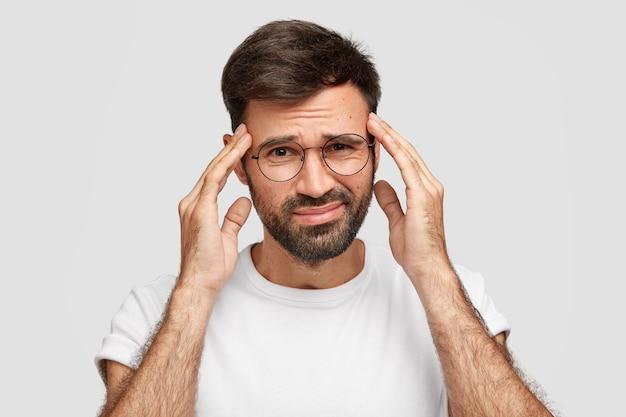 Afbeelding van een ontevreden man met een baard lijdt aan sterke hoofdpijn na een hele nacht werken, heeft een uitdrukking van vermoeidheid, houdt de handen op de slapen, fronst het gezicht, poseert tegen een witte muur. slecht gevoel Gratis Foto