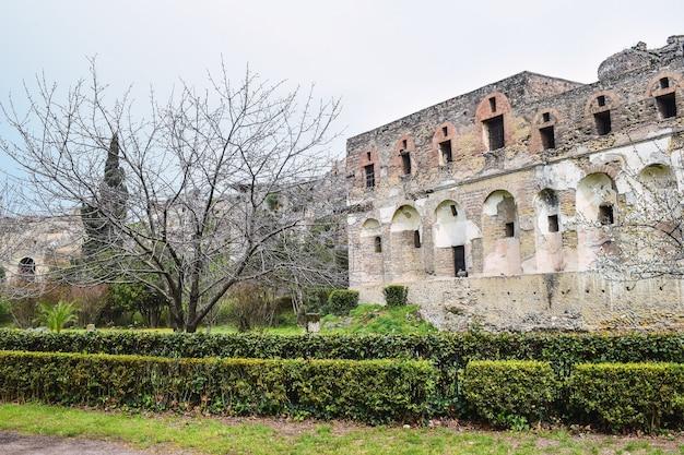 Afbeelding van een ruïne met heggen op de voorgrond onder bewolkte luchten Gratis Foto