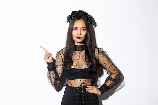 Afbeelding van een teleurgestelde en sceptische aziatische vrouw in heksenkostuum die over iets klaagt, de linkerbovenhoek wijst en ontevreden grimassen trekt, staande op een witte achtergrond in halloween-jurk. Gratis Foto