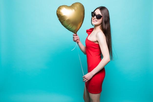 Afbeelding van gemiddelde lengte van prachtige vrouw in mooie rode outfit poseren met hartvorm ballon, geïsoleerd over groene muur Gratis Foto