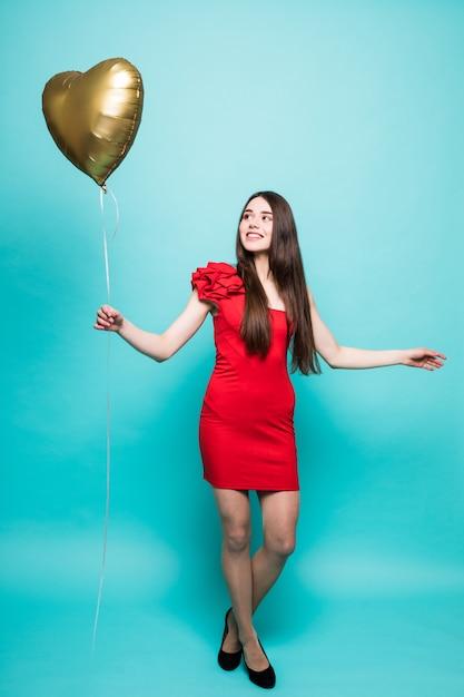 Afbeelding van gemiddelde lengte van prachtige vrouw in mooie rode outfit poseren met hartvorm ballon, geïsoleerd Gratis Foto