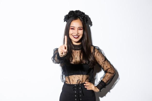 Afbeelding van lachende mooie aziatische vrouw in halloween kostuum met stop gebaar, een vinger uitstrekken en gelukkig kijken, iets verbieden of weigeren, staande witte achtergrond. Gratis Foto