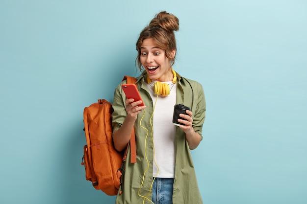 Afbeelding van lachende vrolijke vrouwelijke tiener geniet van communicatie met vriend in groepschat, bekijkt grappige foto's online, luistert offline naar muziek met koptelefoon, drinkt aromatische koffie uit papieren beker Gratis Foto