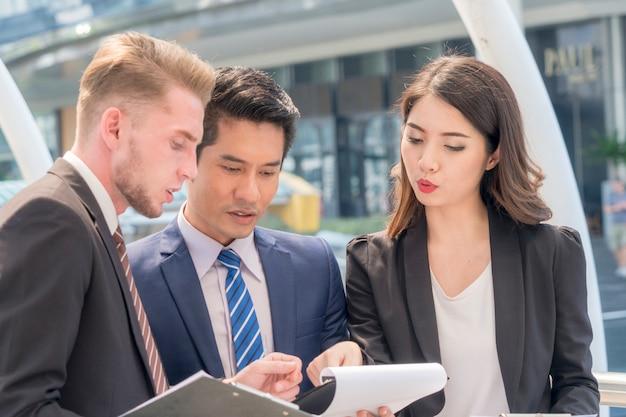 Afbeelding van mensen uit het bedrijfsleven partners bespreken en praten met documenten werk en ideeën tijdens bijeenkomst op buiten voetganger Premium Foto