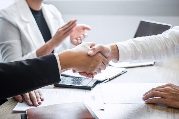 Afbeelding van recruiter in pak en nieuwe medewerker handen schudden en klappen na goede interviews Premium Foto