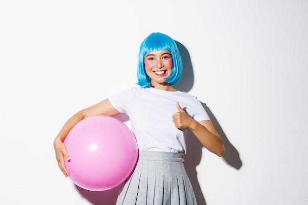 Afbeelding van schattig aziatisch meisje in blauwe pruik en halloween-kostuum, met thumbs-up, met grote roze ballon. Gratis Foto