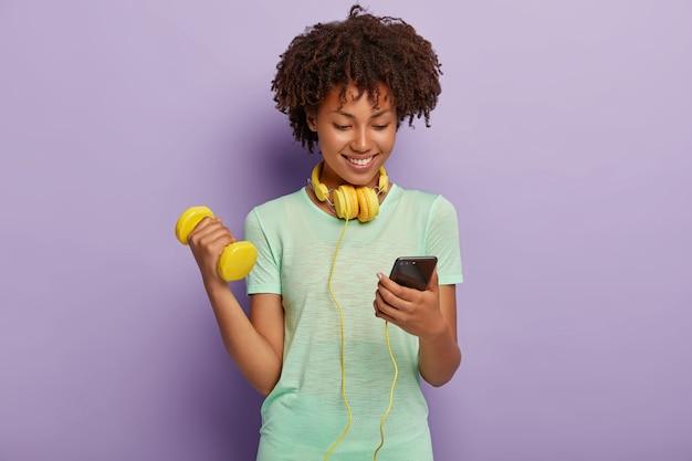 Afbeelding van tevreden donkerharige krullend fit meisje kiest track in afspeellijst, luistert naar muziek via koptelefoon, heft arm op met halter, heeft actieve training, geïsoleerd op violette muur. bodybuilding concept Gratis Foto