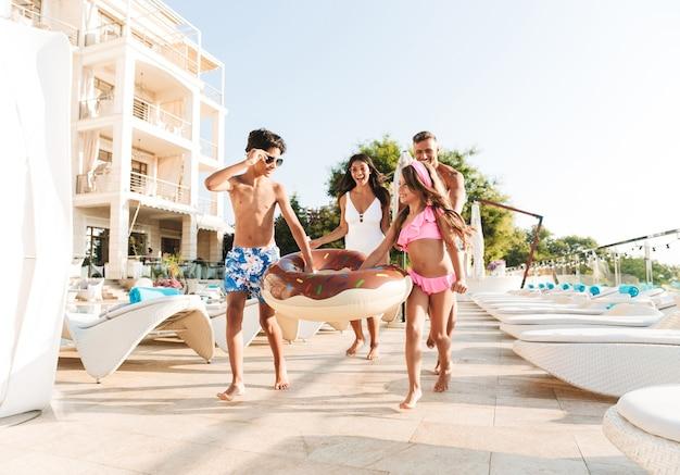 Afbeelding van vakantie gezin met kinderen rusten in de buurt van luxe zwembad, met witte mode ligstoelen en parasols buiten het hotel Premium Foto