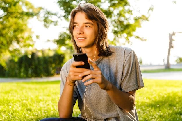Afbeelding van vrolijke jonge kerel luisteren muziek met koptelefoon in het park chatten via de telefoon. Premium Foto