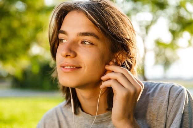 Afbeelding van vrolijke jonge kerel luisteren muziek met koptelefoon in het park. Premium Foto