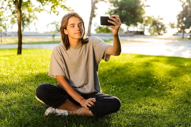 Afbeelding van vrolijke jonge kerel zittend op het gras in het park met behulp van telefoon, neem een selfie. Premium Foto