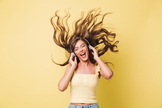 Afbeelding van vrolijke vrouw 20s zingen en genieten van deuntje met haar schudden terwijl u luistert naar muziek via koptelefoon, geïsoleerd op gele achtergrond Premium Foto