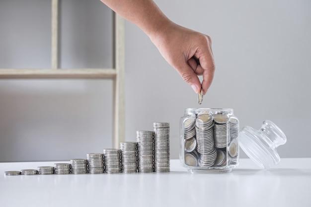 Afbeeldingen van groeiende stapelmunten en hand munt in glazen fles (spaarpot) voor het plannen van meer en besparingen, geld besparen voor toekomstplan en pensioenfondsconcept Premium Foto