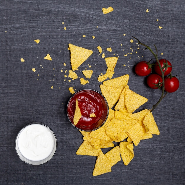 Afgebrokkelde nacho's met dips en tomaten Gratis Foto
