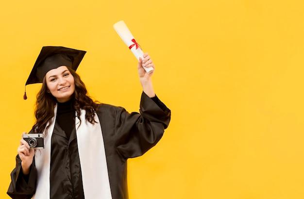 Afgestudeerde student met camera en diploma Gratis Foto