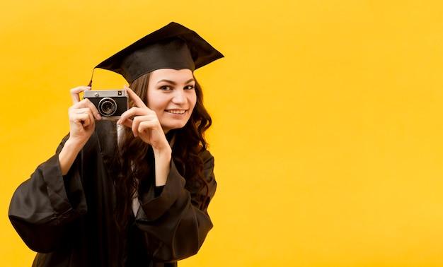 Afgestudeerde student met camera Gratis Foto