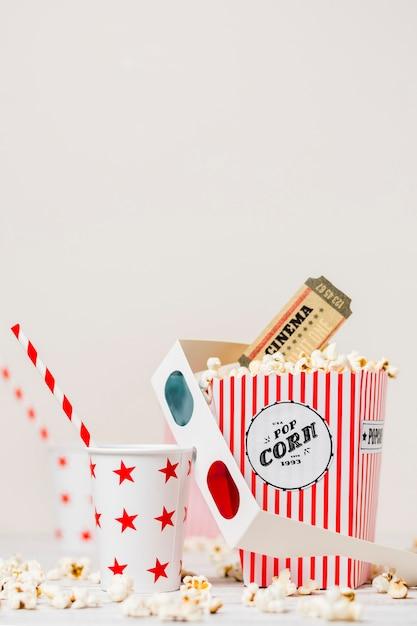 Afhalen van glas met stro; 3d bril; bioscoopkaartjes en popcorndoos tegen witte achtergrond Gratis Foto