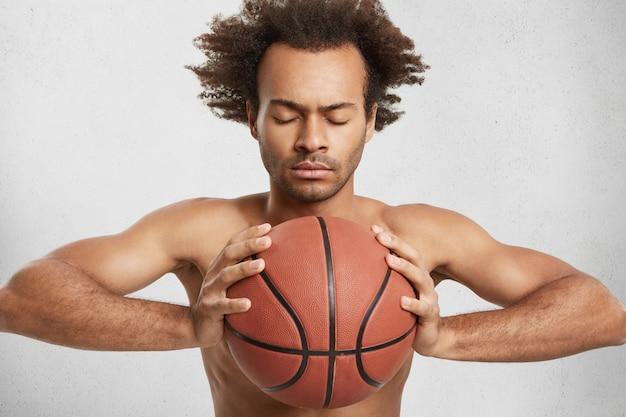African american man sluit ogen, probeert te concentreren als basket bal bezit Gratis Foto