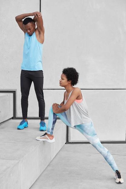 African american mannelijke volwassene werpt handen, opwarmt voor cardiotraining. donkerhuidige vrouw in legging en sneakers strekt zich uit benen, bereidt zich voor op joggen marathon. twee sportieve mensen bij trappen Gratis Foto