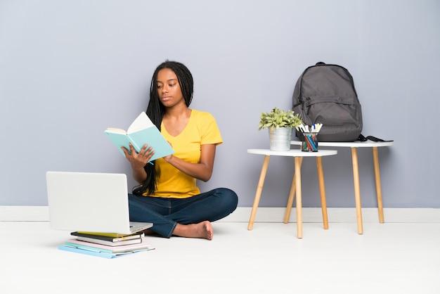 African american tiener student meisje met lang gevlochten haar zittend op de vloer en het lezen van een boek Premium Foto