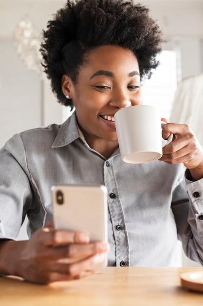 African american vrouw met behulp van een mobiele telefoon Gratis Foto