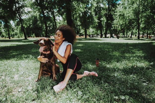 African american vrouw zit met hond. Premium Foto