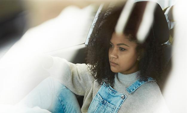 African american vrouw zitten poseren in haar auto Gratis Foto