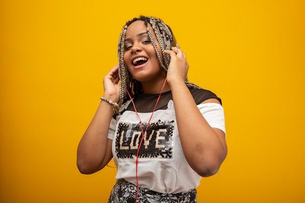 Afrikaans amerikaans meisje dat aan muziek op hoofdtelefoons op geel luistert Premium Foto