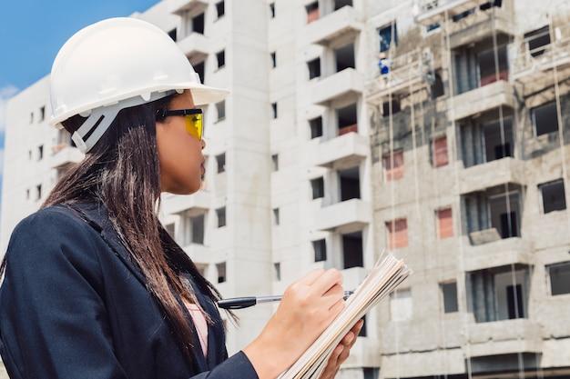 Afrikaanse amerikaanse dame in veiligheidshelm die in blocnote dichtbij dichtbij bouw schrijven Gratis Foto