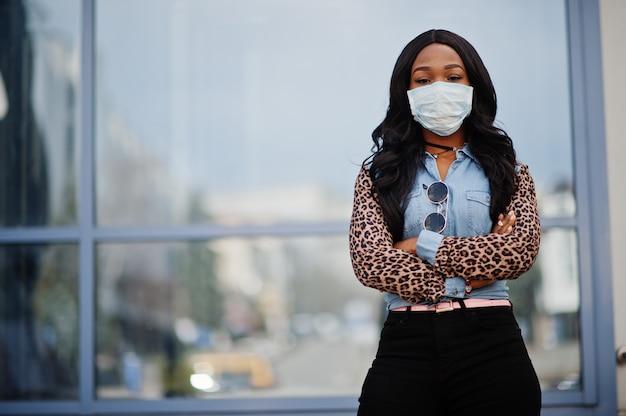 Afrikaanse amerikaanse jonge vrijwilligersvrouw die gezichtsmasker in openlucht draagt. coronavirus-quarantaine en wereldwijde pandemie. Premium Foto