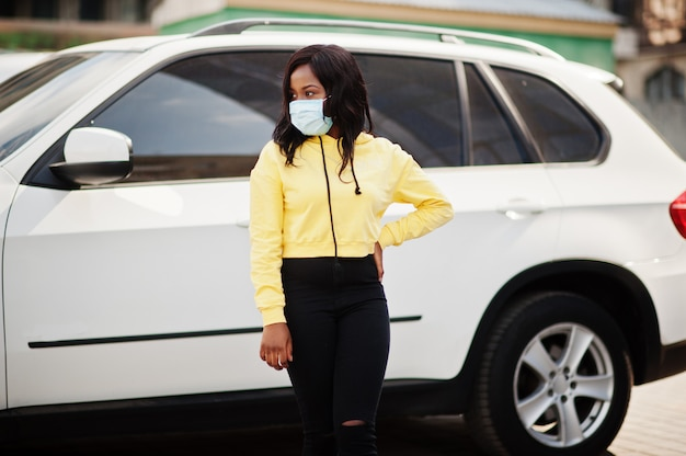 Afrikaanse amerikaanse jonge vrijwilligersvrouw die gezichtsmasker in openlucht draagt tegen suv auto. coronavirus-quarantaine en wereldwijde pandemie. Premium Foto