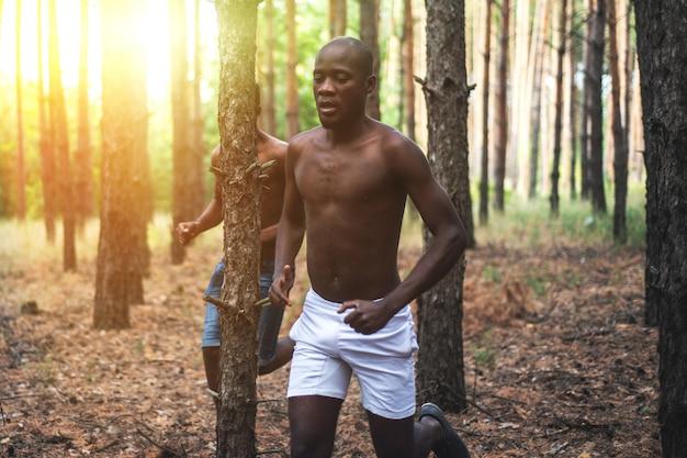 Afrikaanse amerikaanse mannen die in het hout bij zonsondergang lopen. atleten joggen Premium Foto