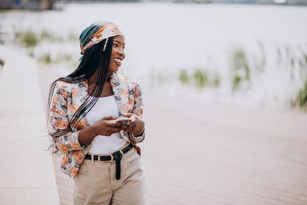 Afrikaanse amerikaanse mens die telefoon in het park met behulp van Gratis Foto
