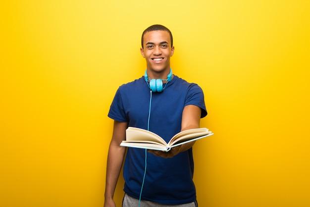 Afrikaanse amerikaanse mens met blauwe t-shirt op gele muur die een boek houdt en het aan iemand geeft Premium Foto