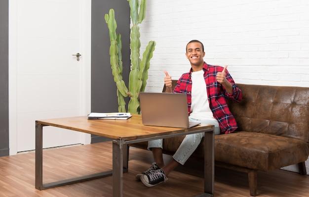 Afrikaanse amerikaanse mens met laptop in woonkamer het geven duimen op gebaar met beide handen en het glimlachen Premium Foto