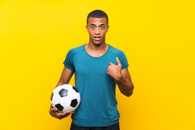 Afrikaanse amerikaanse voetbalstermens met verrassingsgelaatsuitdrukking Premium Foto