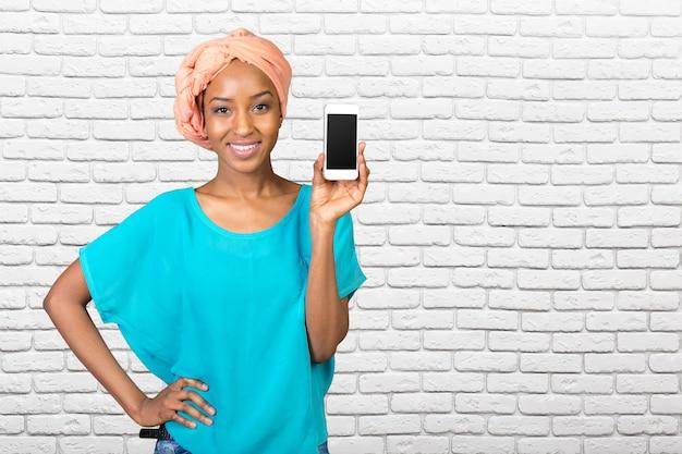 Afrikaanse amerikaanse vrouw die een mobiele telefoon toont Premium Foto