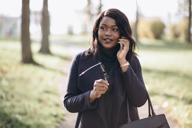 Afrikaanse amerikaanse vrouw die op de telefoon in park spreekt Gratis Foto