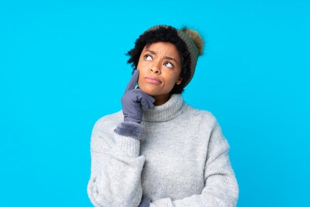 Afrikaanse amerikaanse vrouw met de winterhoed over geïsoleerde blauwe muur Premium Foto