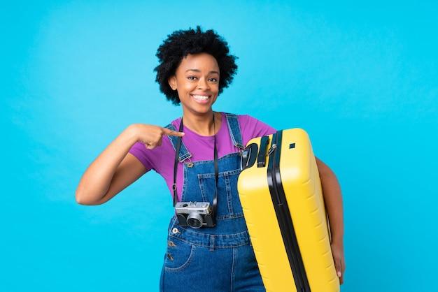 Afrikaanse amerikaanse vrouw met gele koffer over geïsoleerde blauwe muur Premium Foto