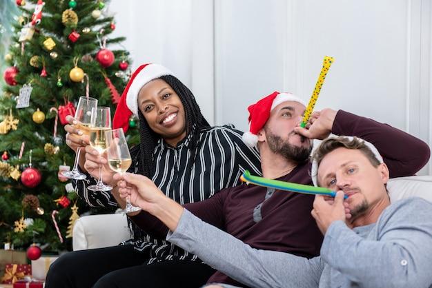 Afrikaanse amerikaanse vrouw met groep vrienden die kerstmis thuis vieren Premium Foto