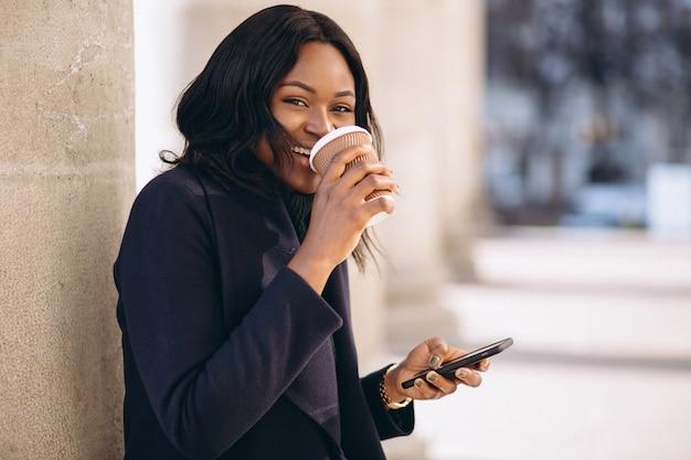 Afrikaanse amerikaanse vrouw met telefoon drinken koffie Gratis Foto