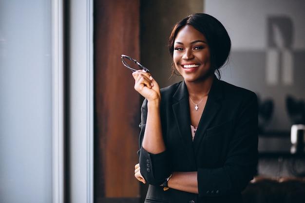 Afrikaanse amerikaanse zakenvrouw bij het raam Gratis Foto