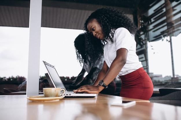 Afrikaanse amerikaanse zakenvrouw met computer en telefoon in een café Gratis Foto