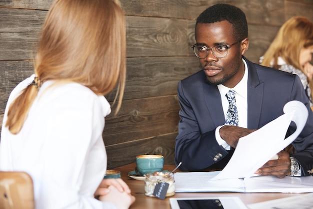 Afrikaanse baas voert een interview met roodharige blanke vrouw Gratis Foto