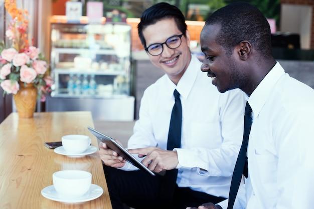 Afrikaanse bedrijfsmens die tablet met aziatische vrienden kijkt Premium Foto